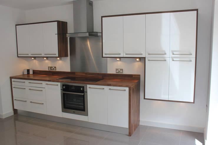 Gloss white wood wrap:  Kitchen by Hallmark Kitchen Designs