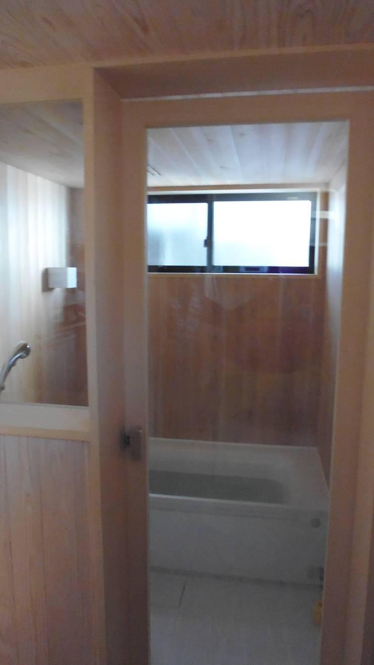 焼き杉と墨入り漆喰と鉄人28号の棟飾りでリノベイト: T設計室一級建築士事務所/tsekkeiが手掛けた浴室です。