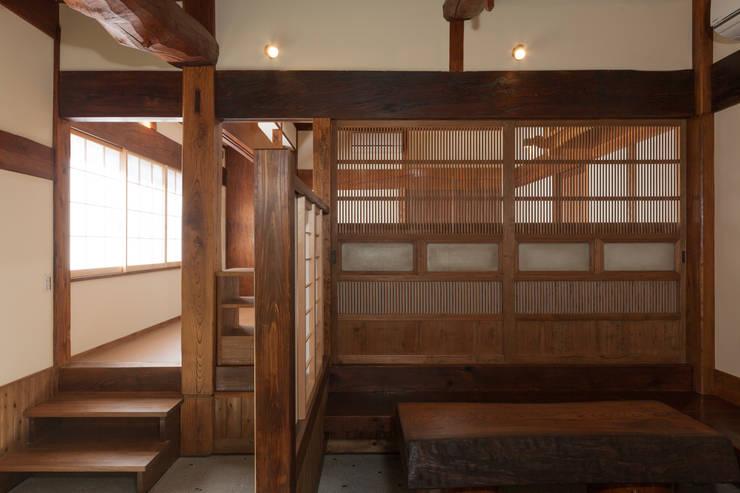生業と共に刻まれた歴史、手斧削りの美しい梁組み: 吉田建築計画事務所が手掛けた壁&床です。
