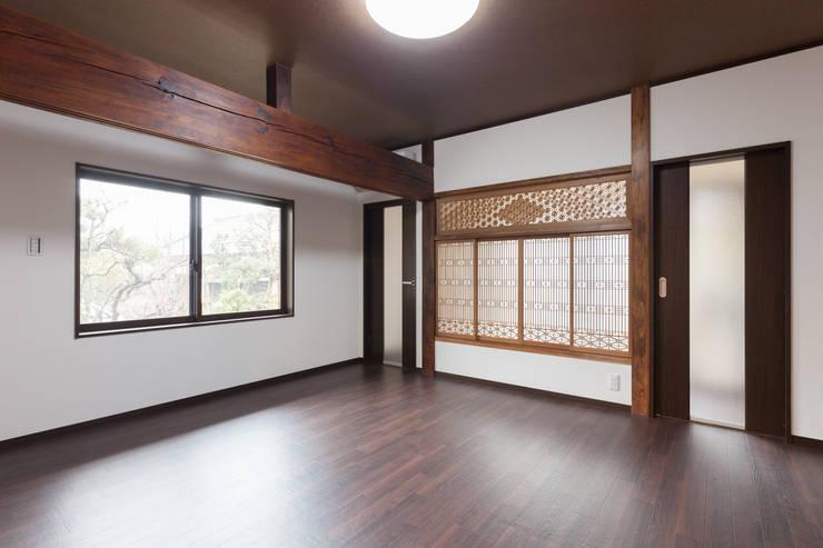 生業と共に刻まれた歴史、手斧削りの美しい梁組み: 吉田建築計画事務所が手掛けたリビングです。