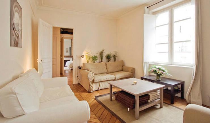 Rénovation d'un appartement haussmannien pour mise en location saisonnière: Salon de style  par Parisdinterieur