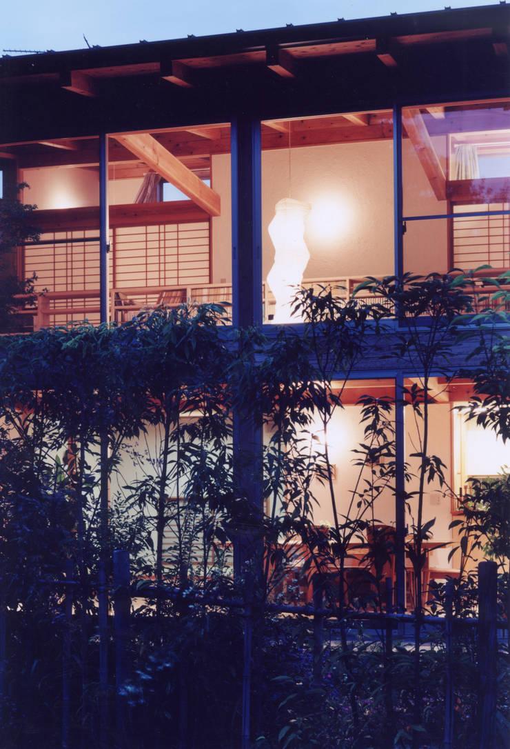 庭からの夜景: ARKSTUDIO一級建築士事務所が手掛けたリビングです。