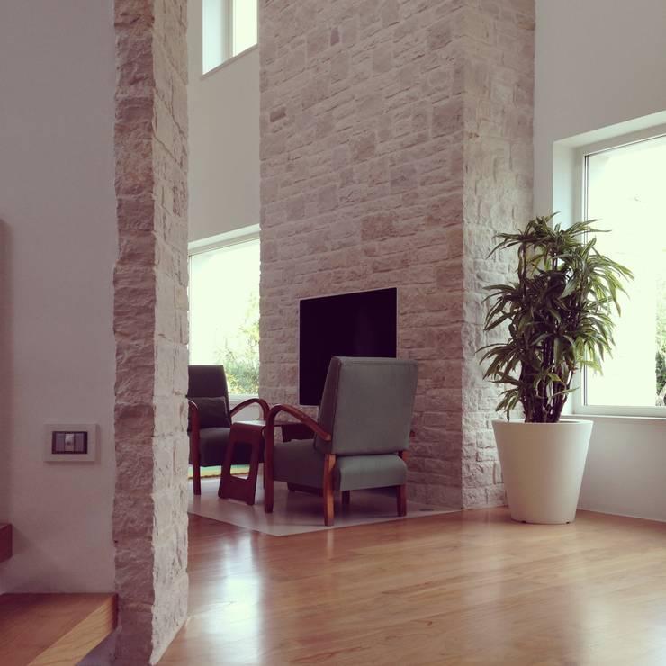 il camino in pietra: Soggiorno in stile  di m12 architettura design