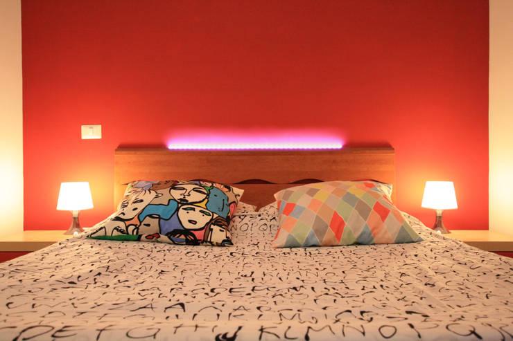 dettaglio della testiera illuminata nella camera da letto matrimoniale: Camera da letto in stile  di EMC2Architetti