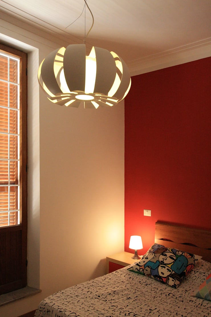 dettaglio del lampadario e della parete rossa nella camera da letto matrimoniale: Camera da letto in stile  di EMC2Architetti