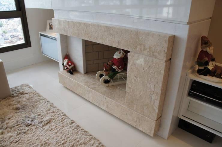 Detalhe lareira em mármore travertino polido: Sala de estar  por Triple Arquitetura