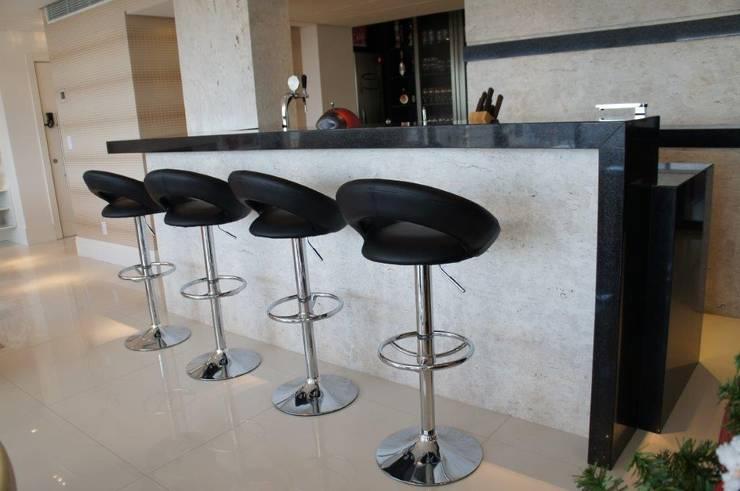 Detalhe balcão bar com chopeira embutida: Salas de estar  por Triple Arquitetura