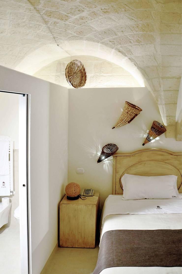Il claustro_Albergo diffuso: Camera da letto in stile  di B+P architetti
