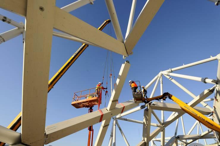 Détail de la charpente en construction: Stades de style  par Wilmotte & Associés