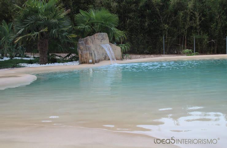Paisajismo en un jardín con una piscina de arena.: Piscinas de estilo  de Ideas Interiorismo Exclusivo, SLU