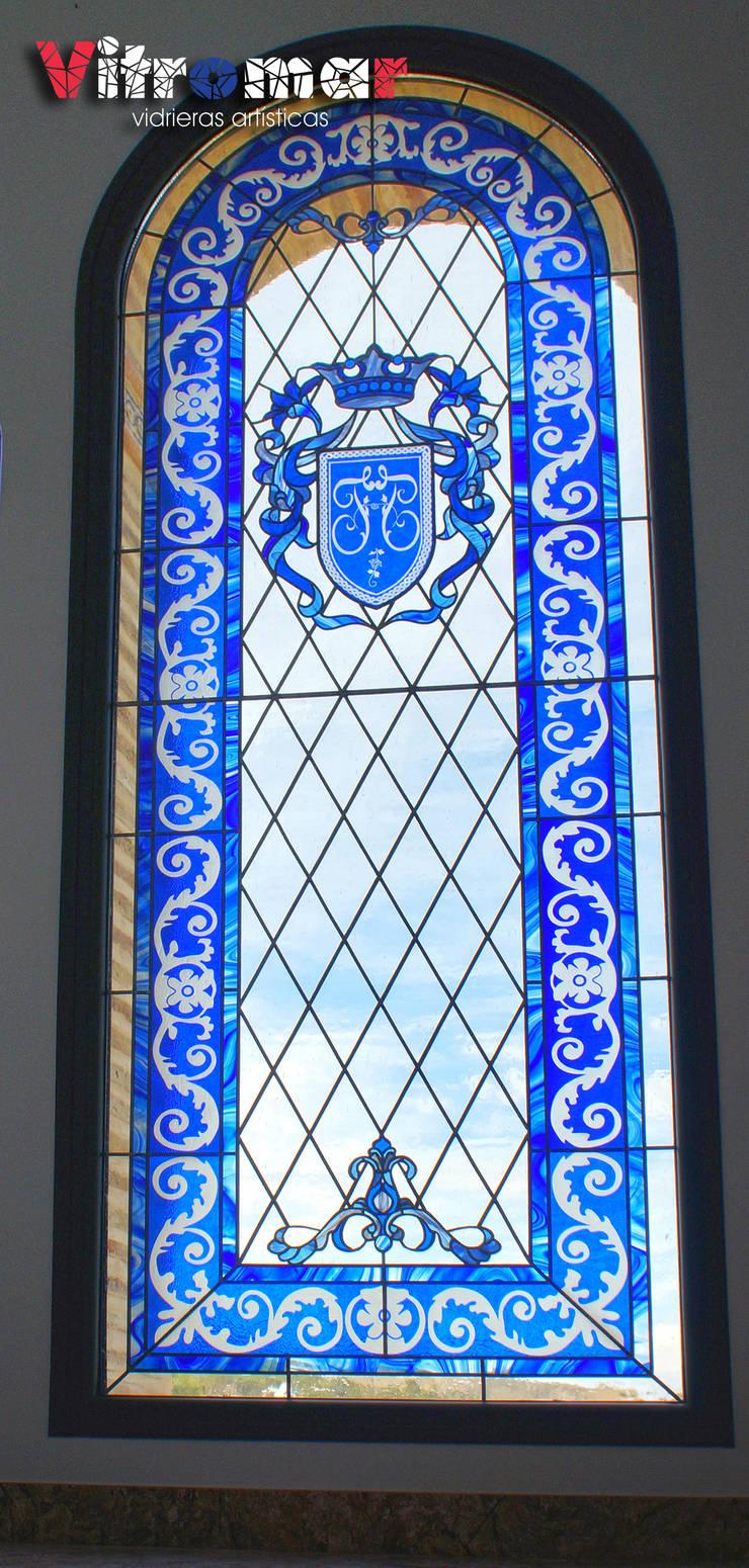Vidreira azul con escudo tallado: Puertas y ventanas de estilo  de Vitromar Vidrieras Artísticas
