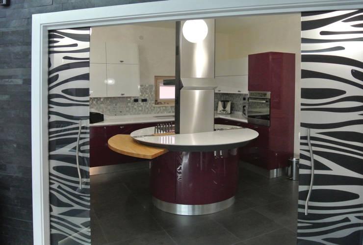 la cucina vista dalla zona giorno attraverso la porta scorrevole in vetro:  in stile  di GIOIA Biagio ARCHITETTO