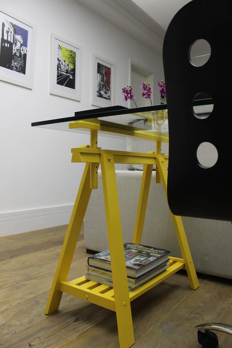 Detalhe do cavalete amarelo em composição com livros e quadros adquiridos em viagens pelos proprietários. por Ana Carolina Cardoso Arquitetura e Design Moderno