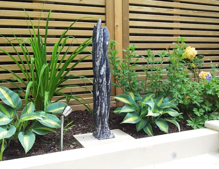 Sculpture with Hostas, Day Lily and Rose:  Garden by Gardenplan Design