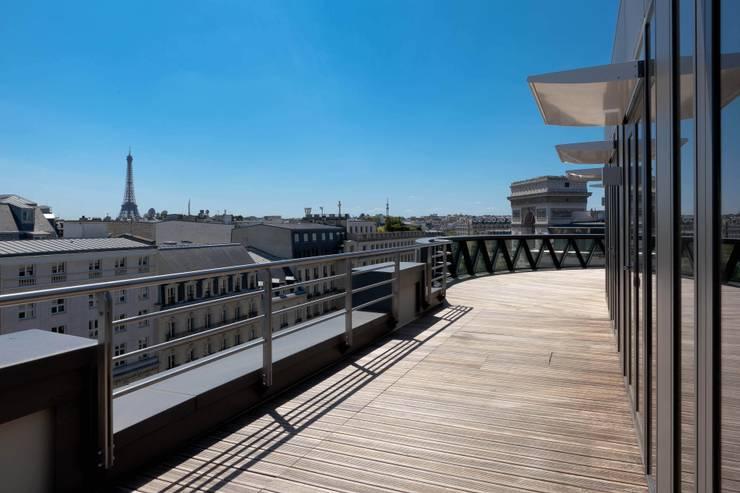 Vue de l'Arc de Triomphe et la Tour Eiffel depuis la terrasse en toiture: Bureau de style  par braun + associés architectes
