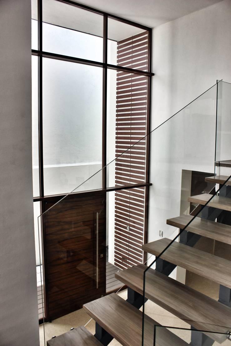 Casa Jurica: Pasillos y recibidores de estilo  por REM Arquitectos