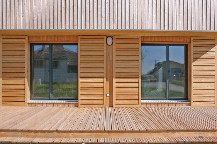 Vue des baies de l'espace du séjour en rez-de-chaussée de la façade sud (détail): Maisons de style  par ABA - Architecture Bioclimatique Auvergne