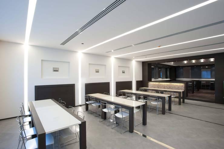 Guess Building: Negozi & Locali commerciali in stile  di Giraldi Associati Architetti