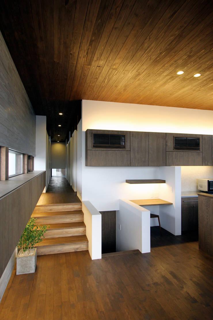 丘の上の二世帯住宅: 時空遊園 JIKOOYOOEN ARCHITCTSが手掛けた廊下 & 玄関です。