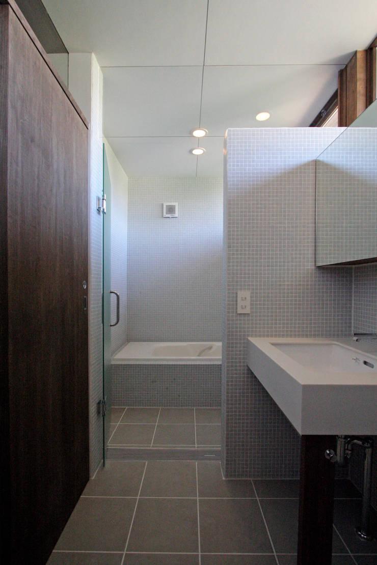 丘の上の二世帯住宅: 時空遊園 JIKOOYOOEN ARCHITCTSが手掛けた浴室です。