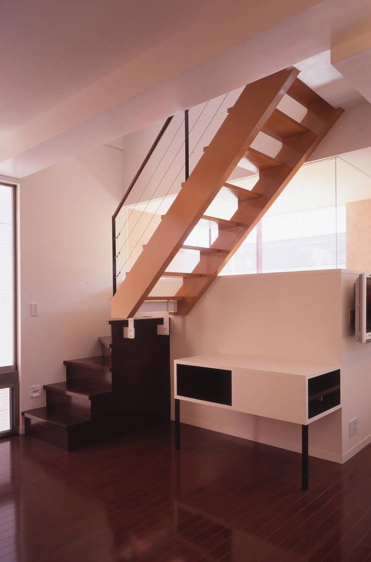 3階への階段 奥は店舗待合いの吹抜け: 北川裕記建築設計が手掛けた廊下 & 玄関です。