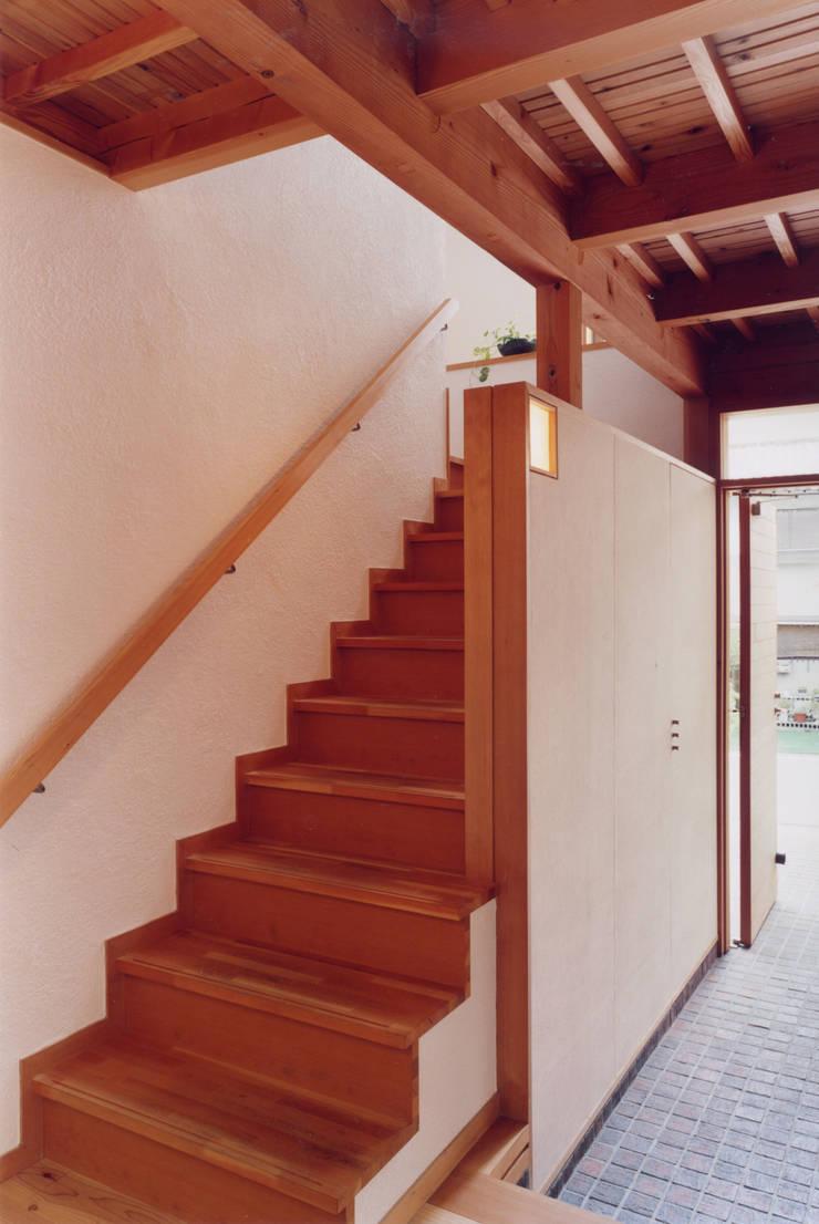 階段横の和紙の壁の照明と収納スペース隠し扉: ARKSTUDIO一級建築士事務所が手掛けた廊下 & 玄関です。