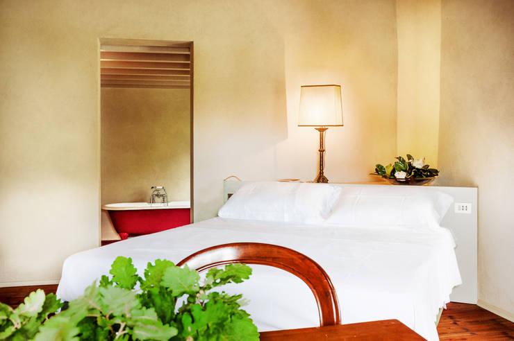 65 - Suite 3 - Stanza da letto, in secondo piano soggiorno con vasca da bagno: Camera da letto in stile  di Studio Athesis