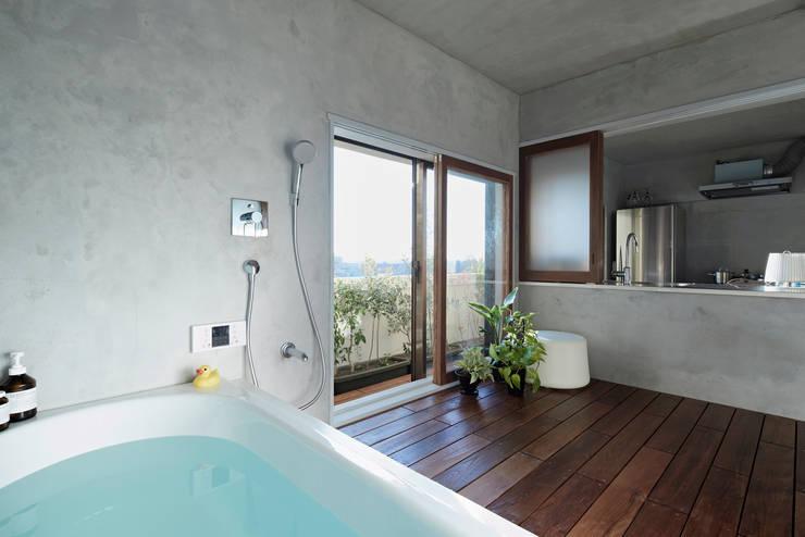 大きな窓のあるバスルーム: Takeshi Shikauchi Architect Office/鹿内健建築事務所が手掛けた浴室です。,