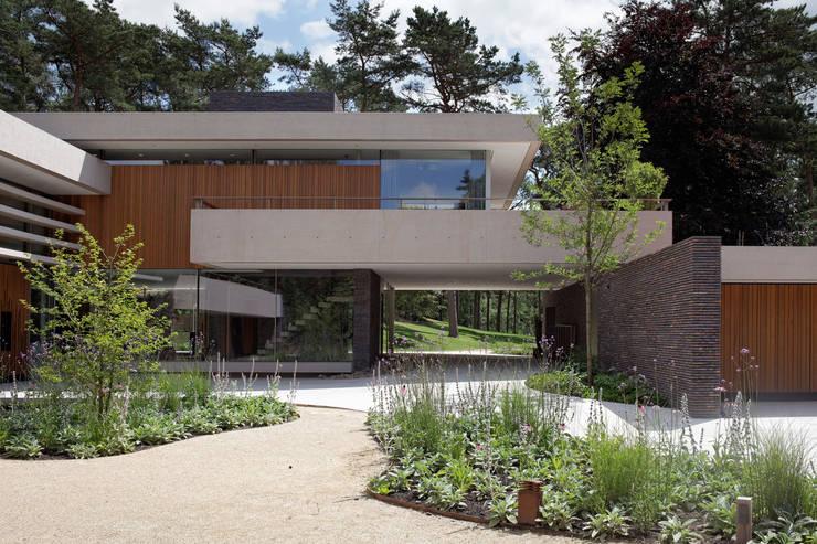 De onderdoorgang verbindt de gecultiveerde voorhof met het bos achter de duinvilla.: moderne Huizen door HILBERINKBOSCH architecten