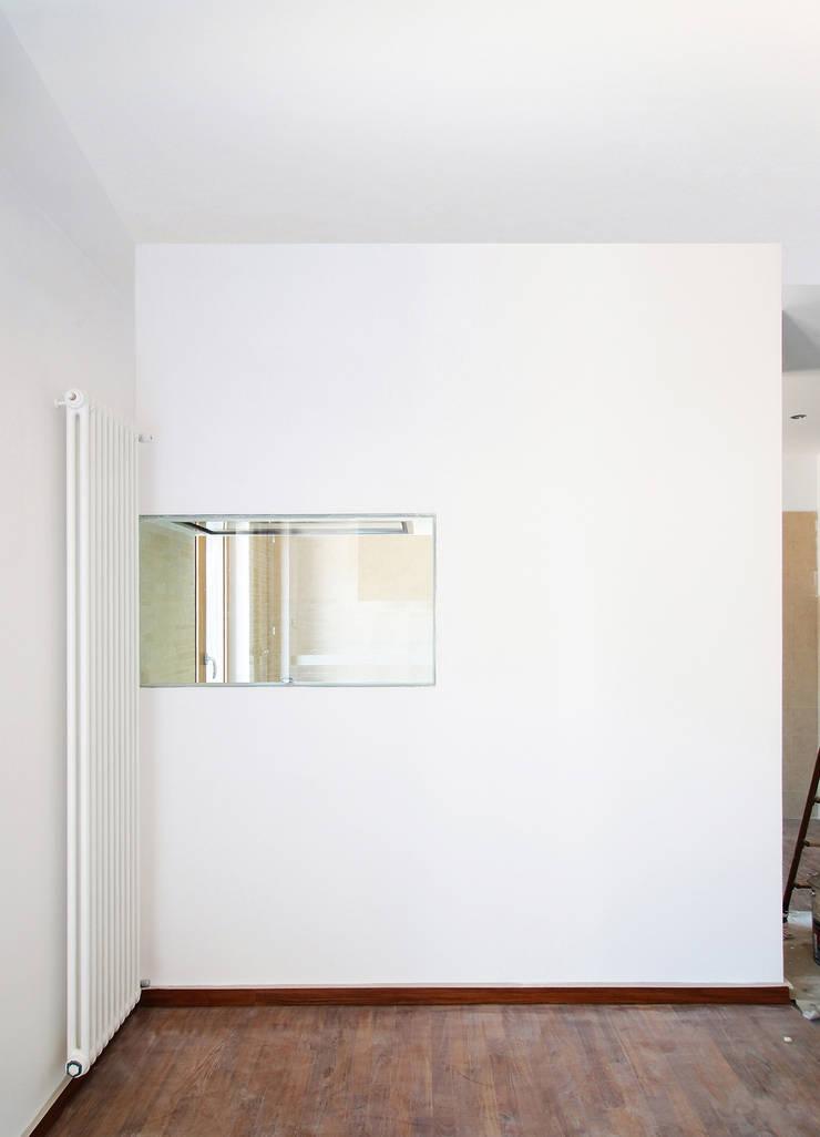 la parete che cela la cucina:  in stile  di Giancarlo Covino