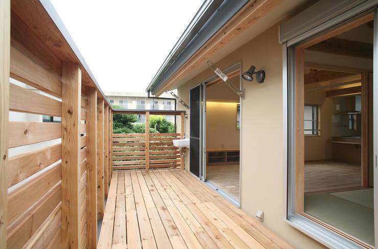 居間と繋がるデッキ: 八島建築設計室が手掛けたテラス・ベランダです。,