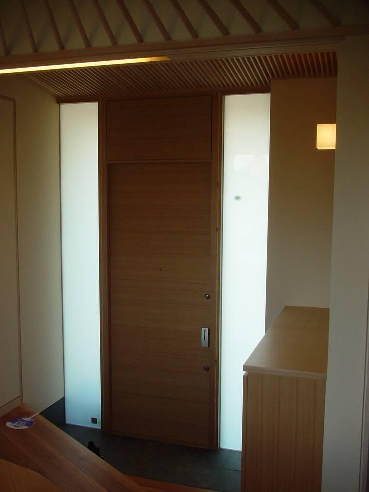 玄関室内: 牧野建築計画が手掛けた窓です。