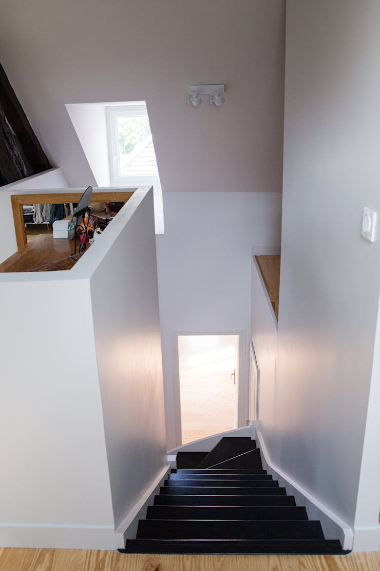 Un escalier noir et blanc épuré: Couloir et hall d'entrée de style  par mllm