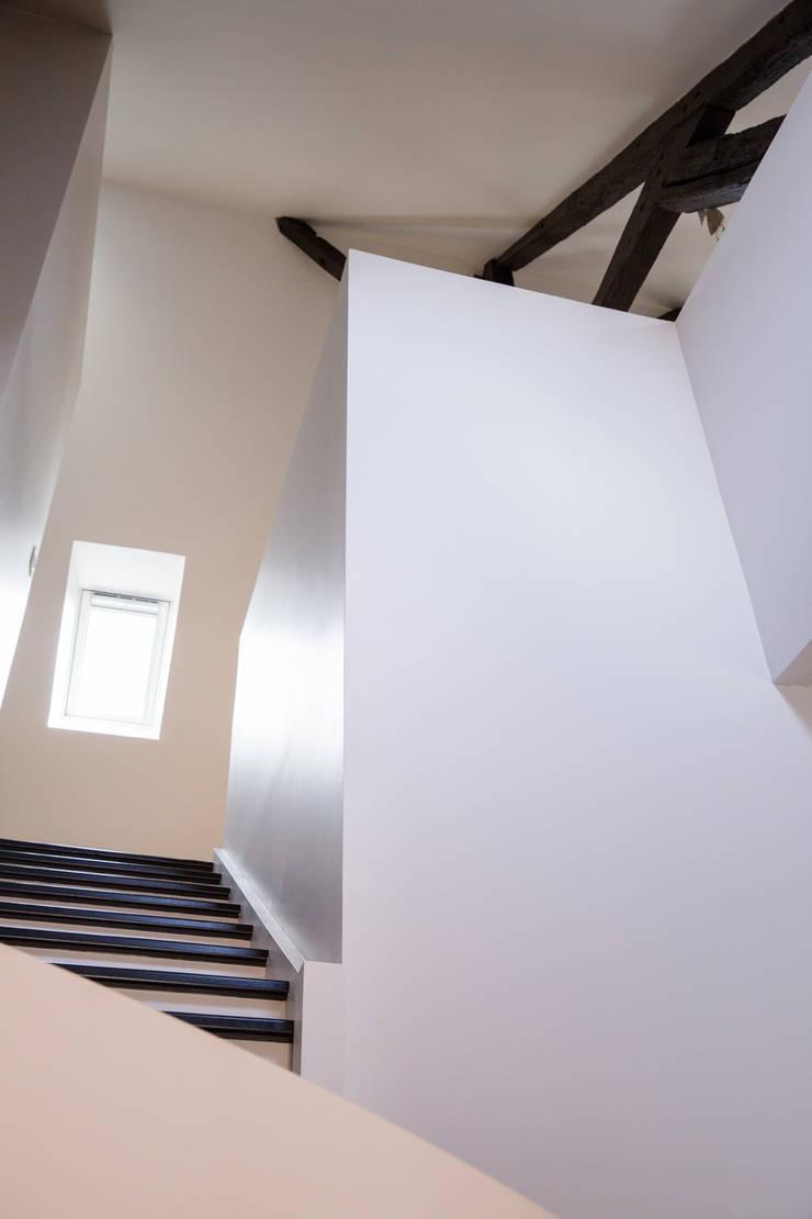 Jeu de volumes blancs: Couloir et hall d'entrée de style  par mllm