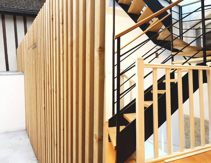 Escalier et habillage cour se répondent: Maisons de style  par CRISS CROSSING