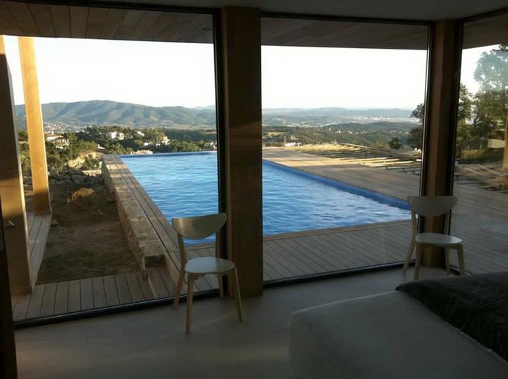 Zicht op het zwembad vanuit de woonkamer:  Woonkamer door TenBrasWestinga ARCHITECTUUR / INTERIEUR en STEDENBOUW, Mediterraan