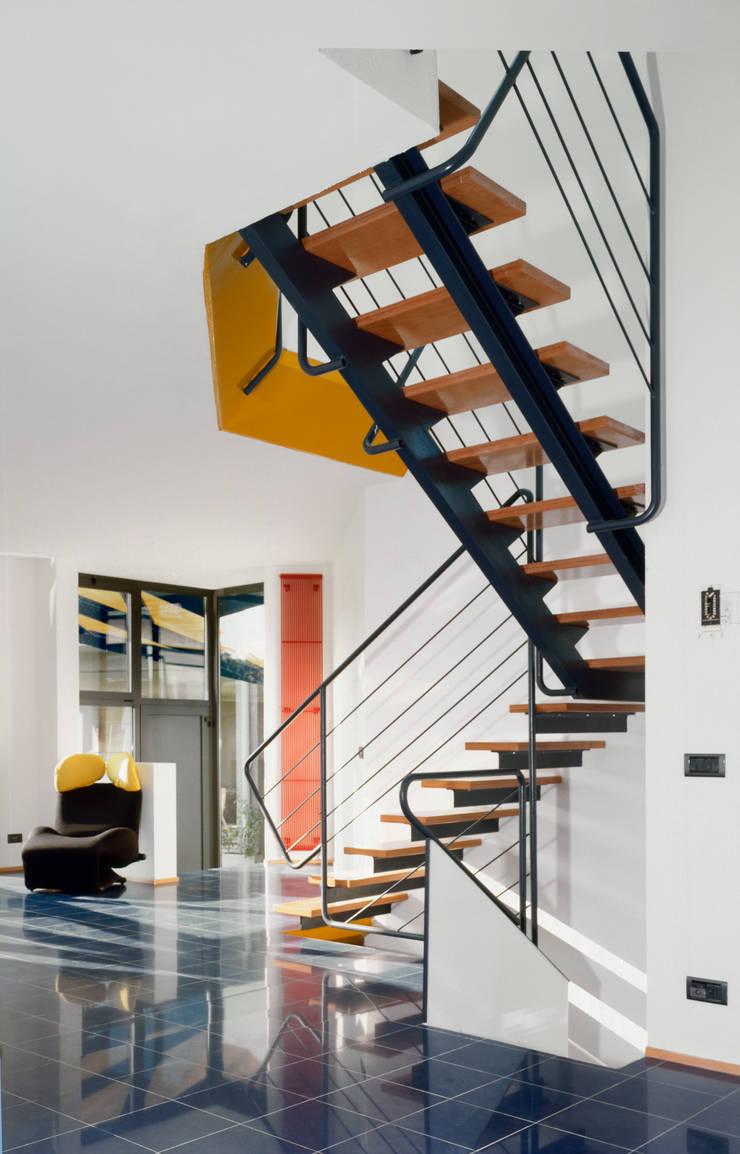 l'ingresso e la scala che personalizza e divide la zona giorno e la cucina: Ingresso & Corridoio in stile  di RoccAtelier Associati