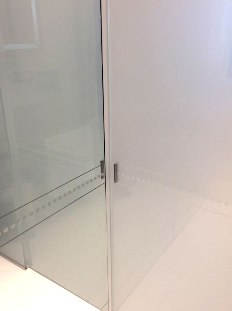 Particolare pannello scorrevole e pannello a specchio con serigrafia: Hotel in stile  di Difinoarchitetti