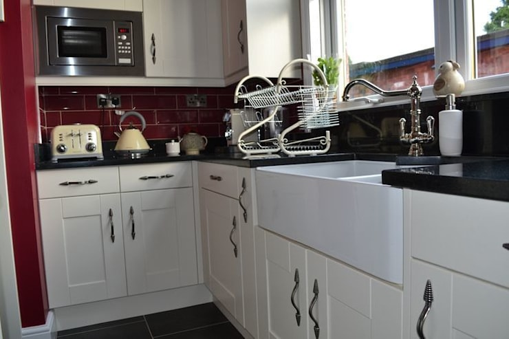 Wentworth Kitchen Units in Alabaster with black granite worktops and cranberry wall tiles.:   by Statement Kitchens