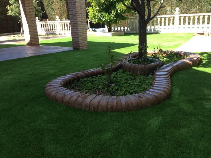 Jardin con césped artificial: Jardines de estilo  de Allgrass Solutions