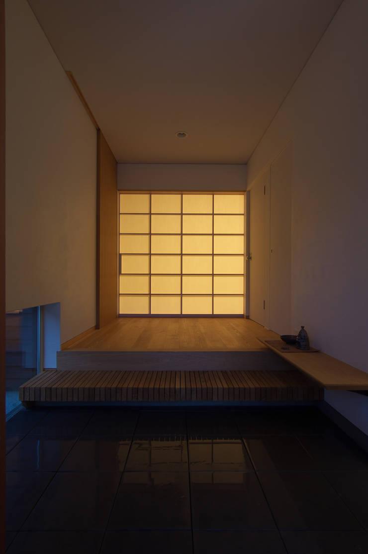 玄関の光壁: DEMU建築設計事務所が手掛けた壁です。