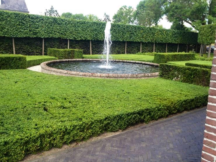 Landschappelijke tuin met fontein van IJsselsteentjes:  Tuin door Stam Hoveniers