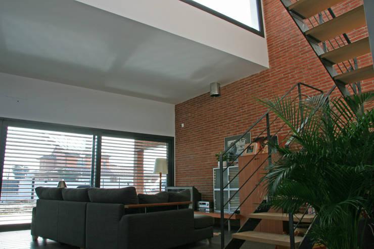 Salón, con escaleras hacia la primera planta: Salones de estilo  de FG ARQUITECTES