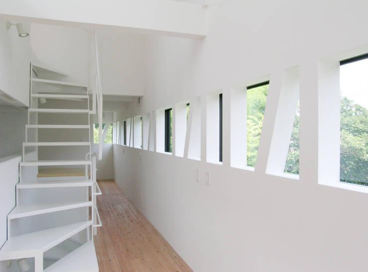 2階子世帯リビングから廊下を見る。水平連続窓が東側のパノラマ状の風景へと開く: 株式会社小島真知建築設計事務所 / Masatomo Kojima Architectsが手掛けた廊下 & 玄関です。