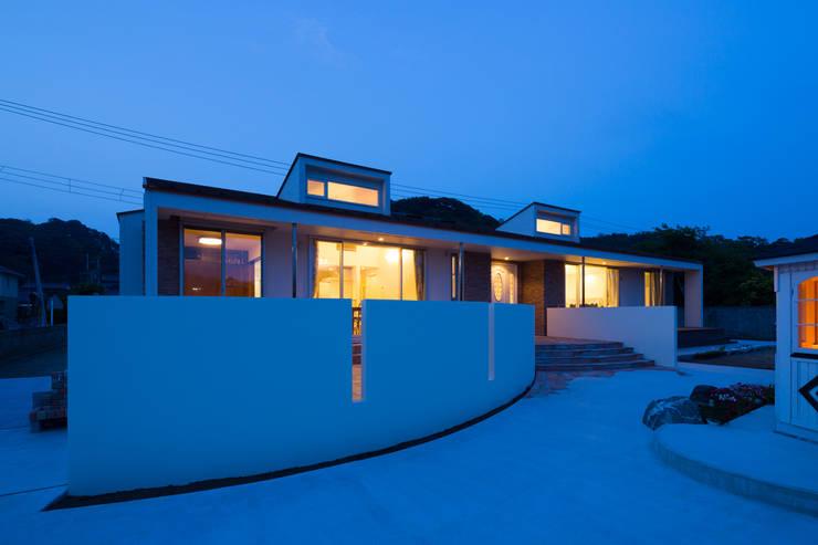 建物全景夕景: 菅原浩太建築設計事務所が手掛けた家です。