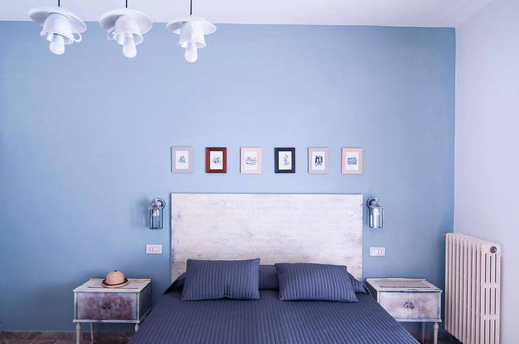 """Camera """"Il Cappellaio Matto"""": Hotel in stile  di Studio Giorgi Barbieri Architetti"""