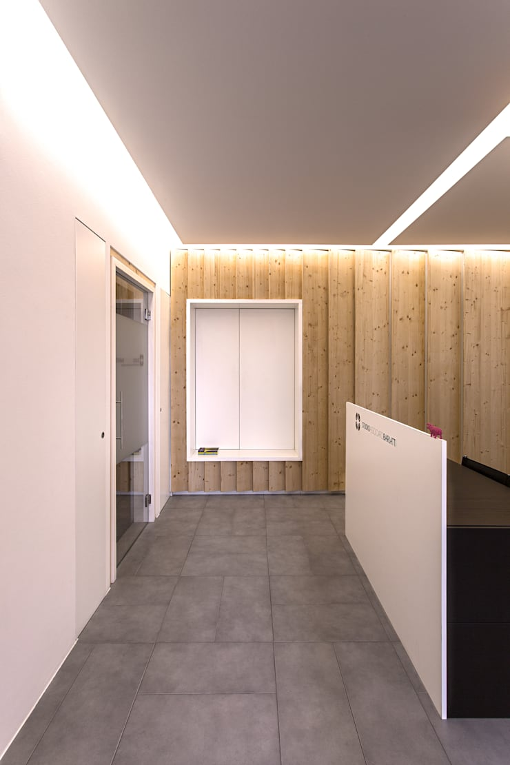 La boiserie in legno e la nicchia per l'attesa: Studio in stile  di PLUS ULTRA studio, Moderno