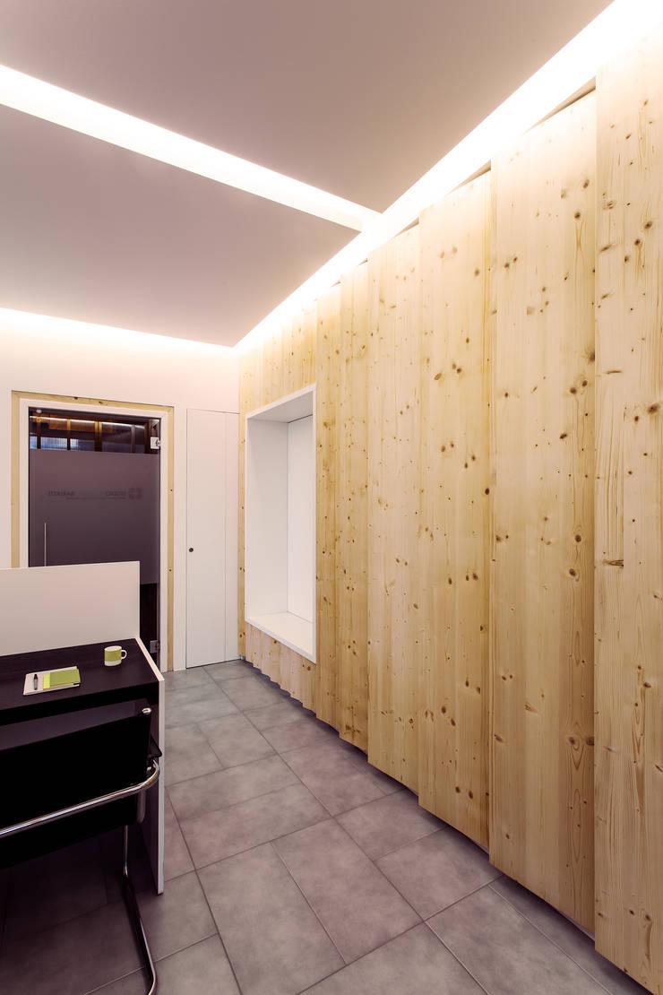La boiserie-contenitore in abete: Studio in stile  di PLUS ULTRA studio, Moderno