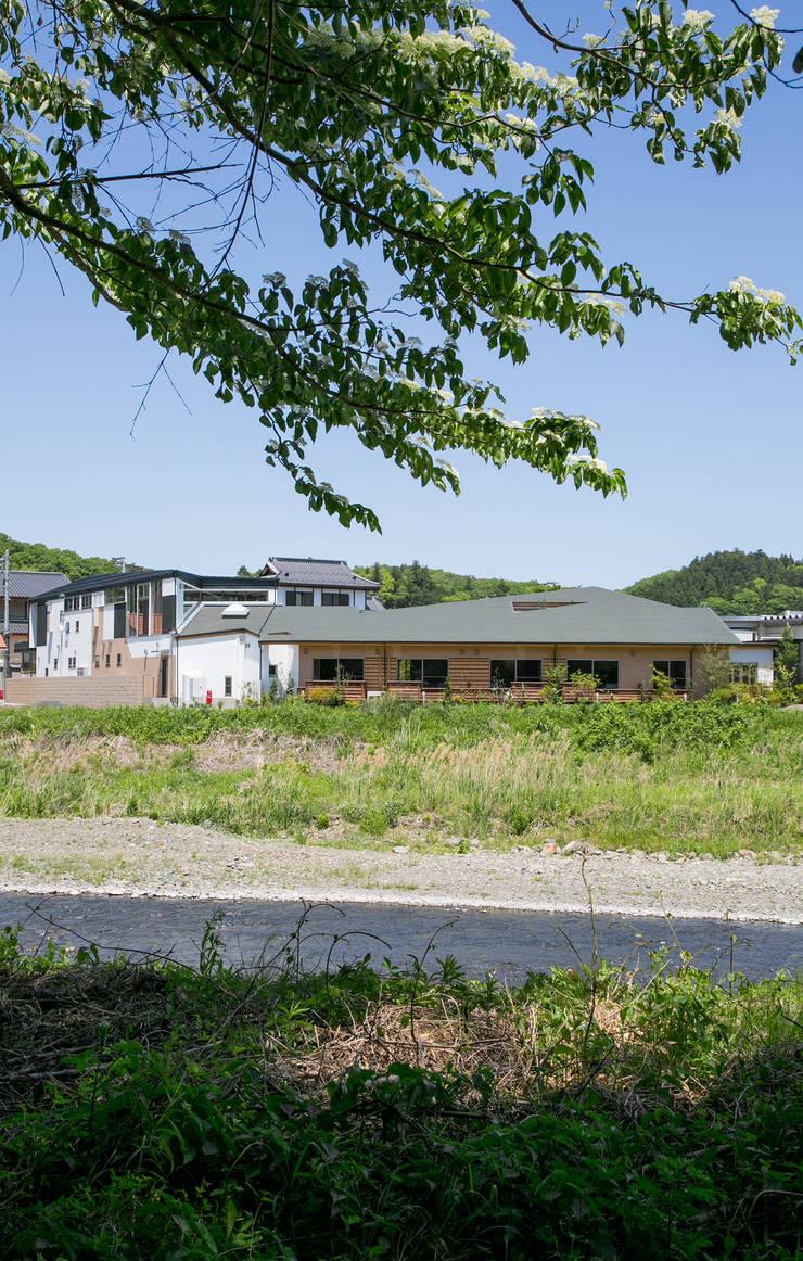 川の反対側からの外観: 有限会社加々美明建築設計室が手掛けた商業空間です。,