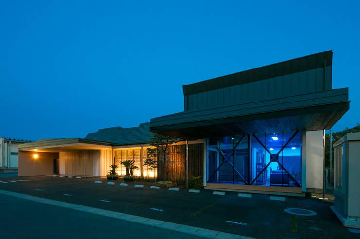 北側エントランス 夕景: 有限会社加々美明建築設計室が手掛けた商業空間です。,